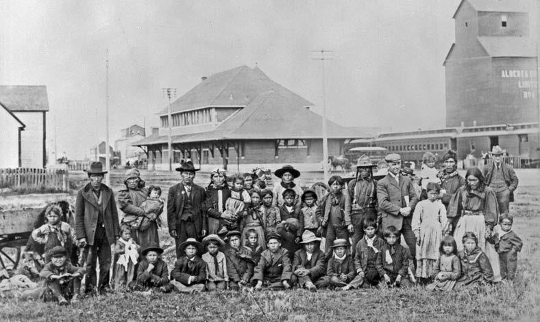 A group of students and parents from the Saddle Lake Reserve, en route to the Methodist-operated school in Red Deer, Alberta. Woodruff, Library and Archives Canada, PA-040715.